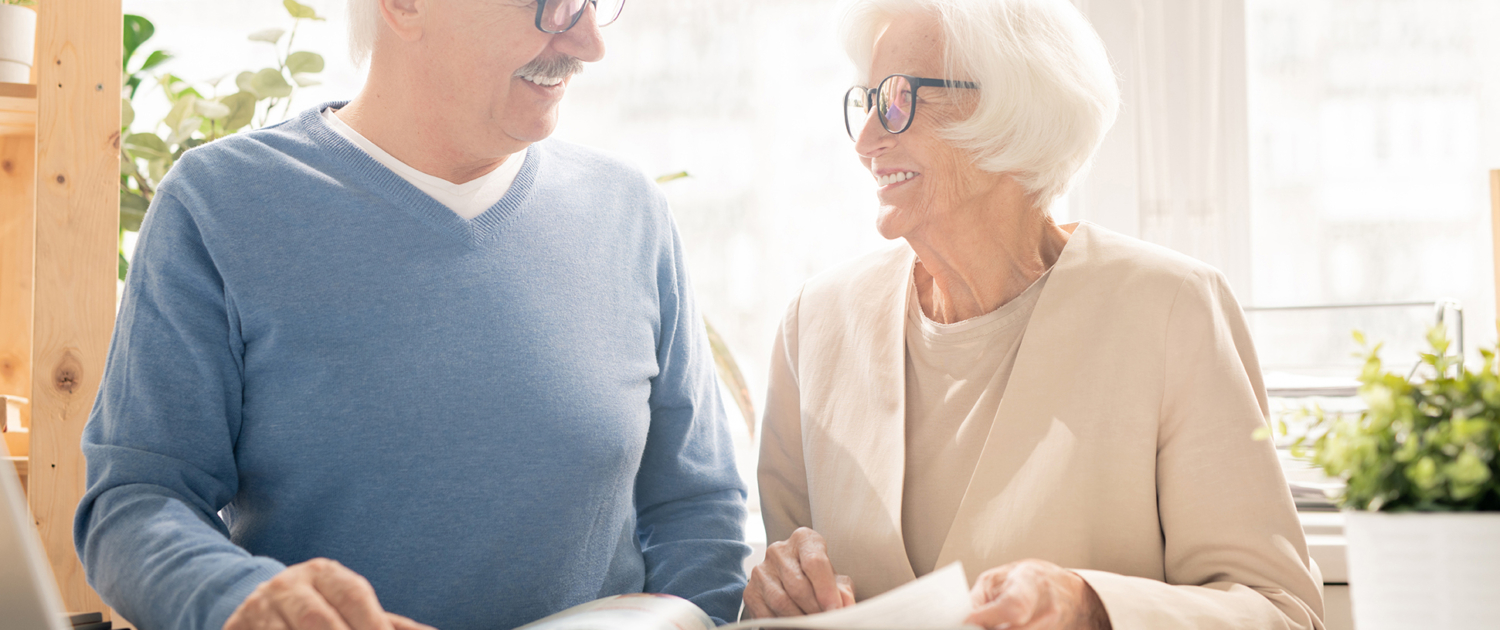 Older man and woman smiling while looking at an information guide