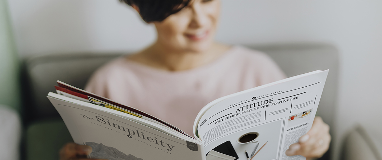 Woman sitting and reading a magazine or journal