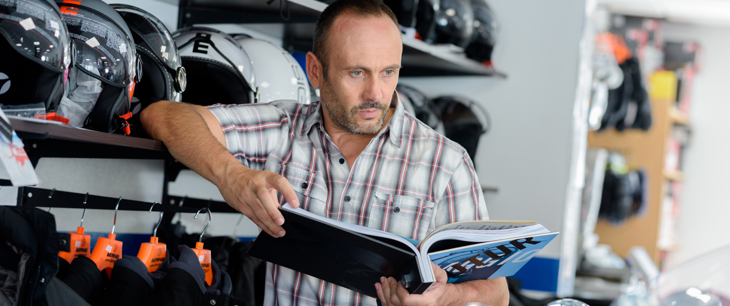 Man holding a product manual in a motorcycle shop